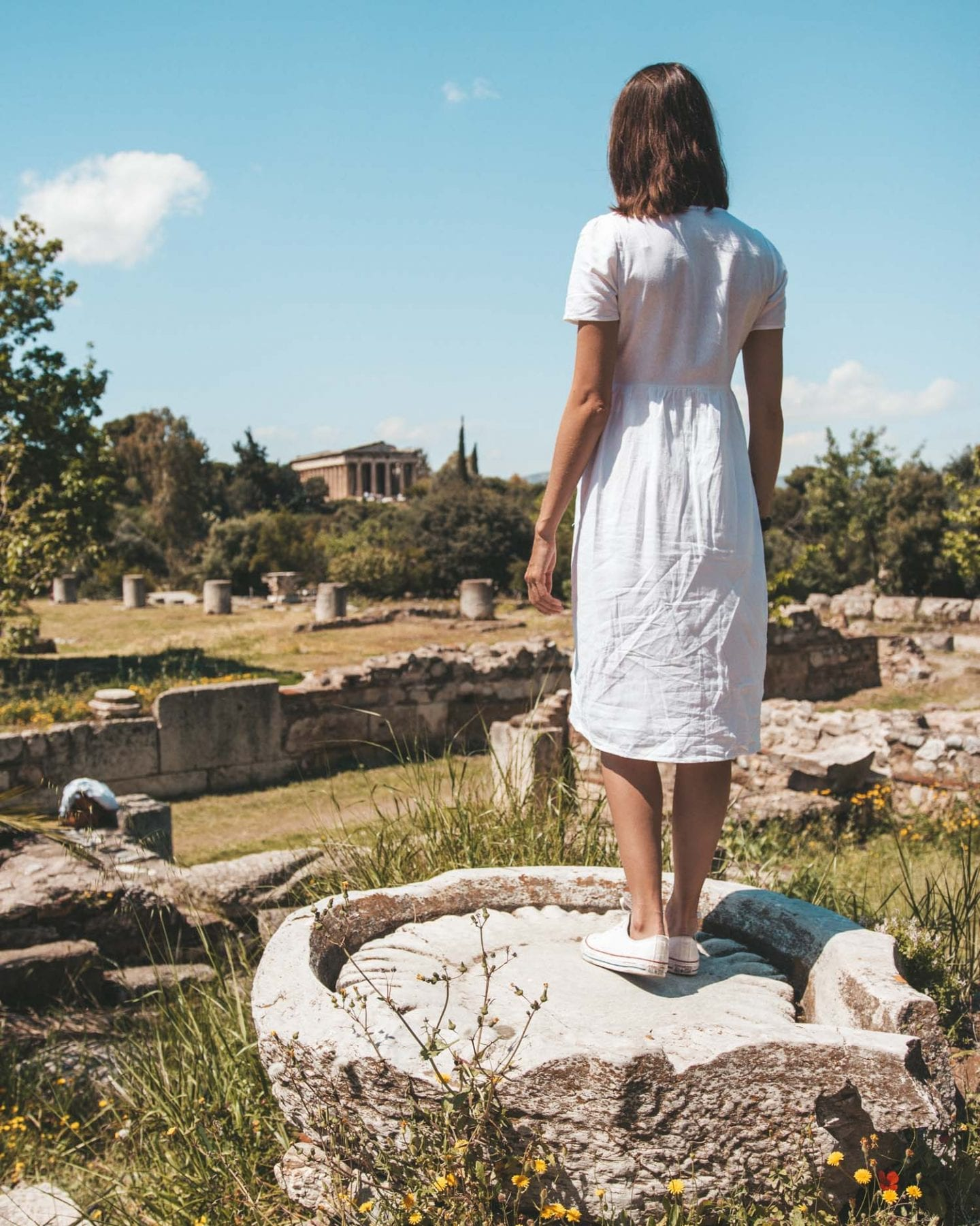 girl standing on ruins in the ancient agora
