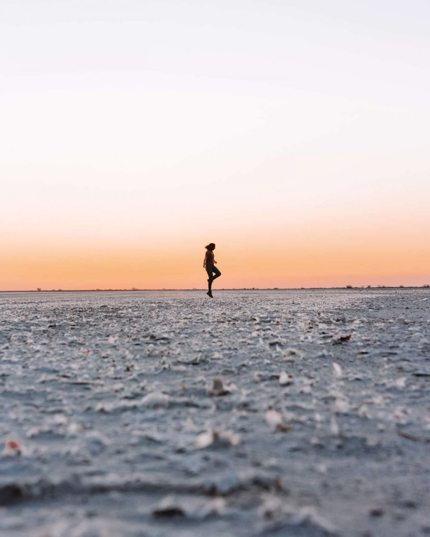 girl standing on salt pan in botswana