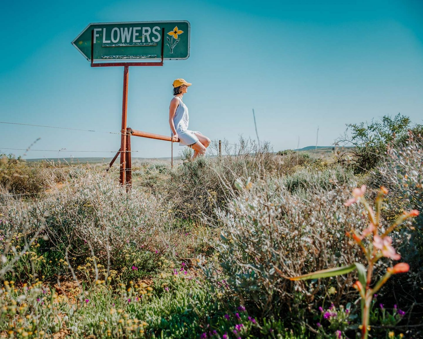 girl sitting next to flower sign